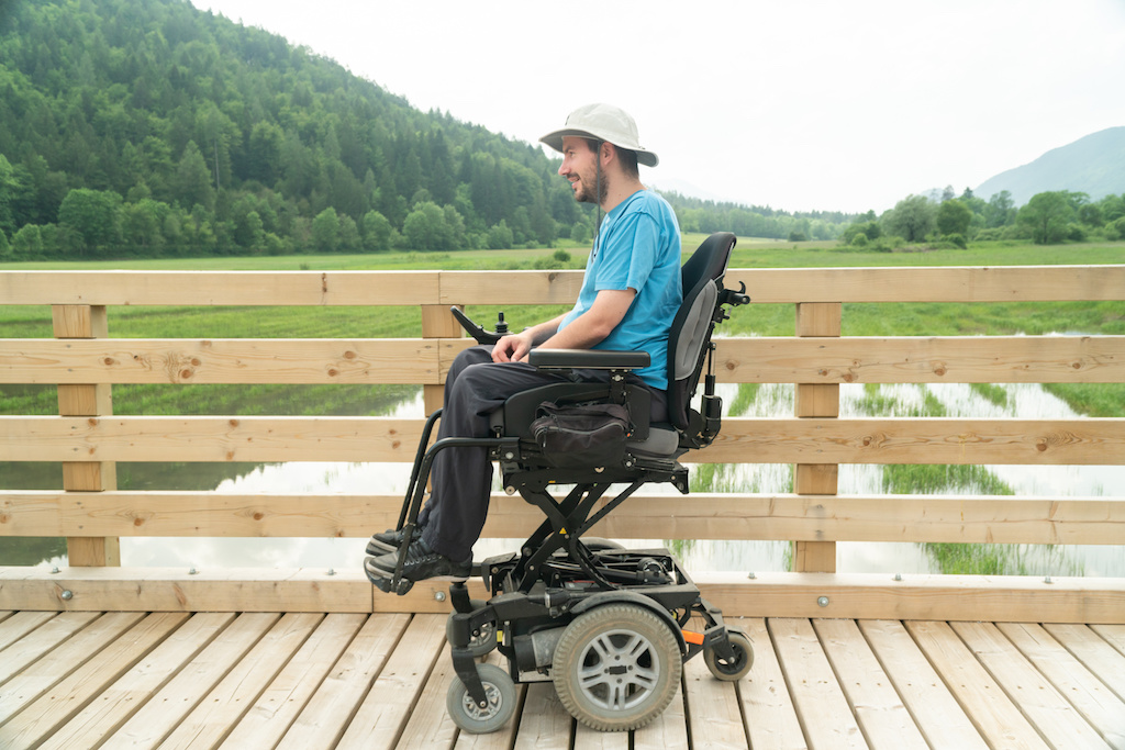 Photo of disabled Young man in electric wheelchair on a boardwalk enjoying his freedom and observing nature