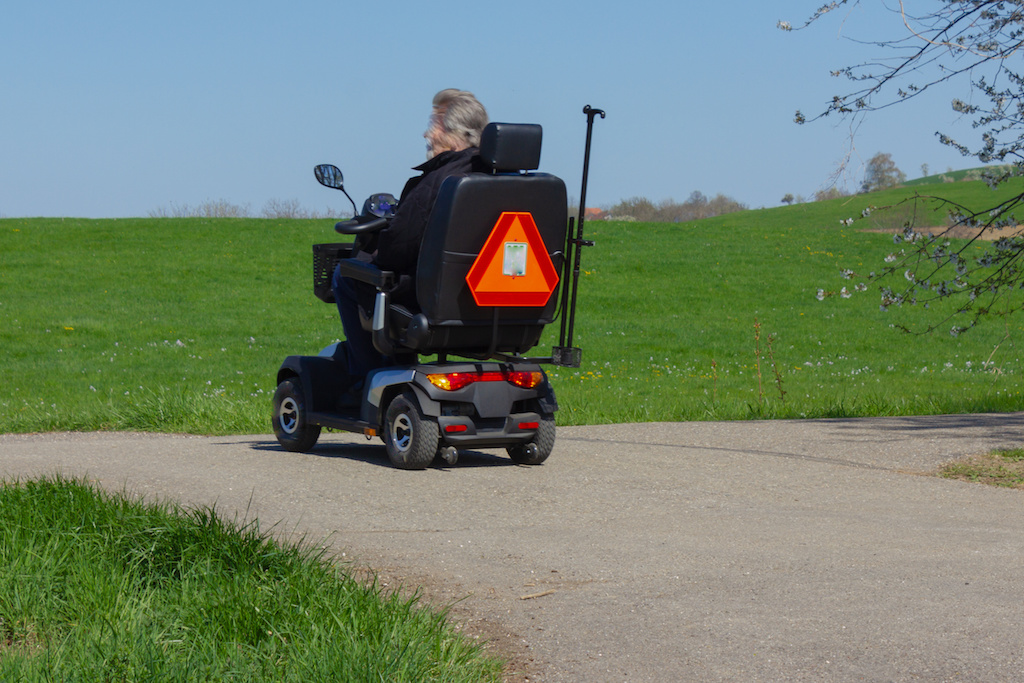 motor wheelchair in south germany bikeway at april springtime sunny afternoon
